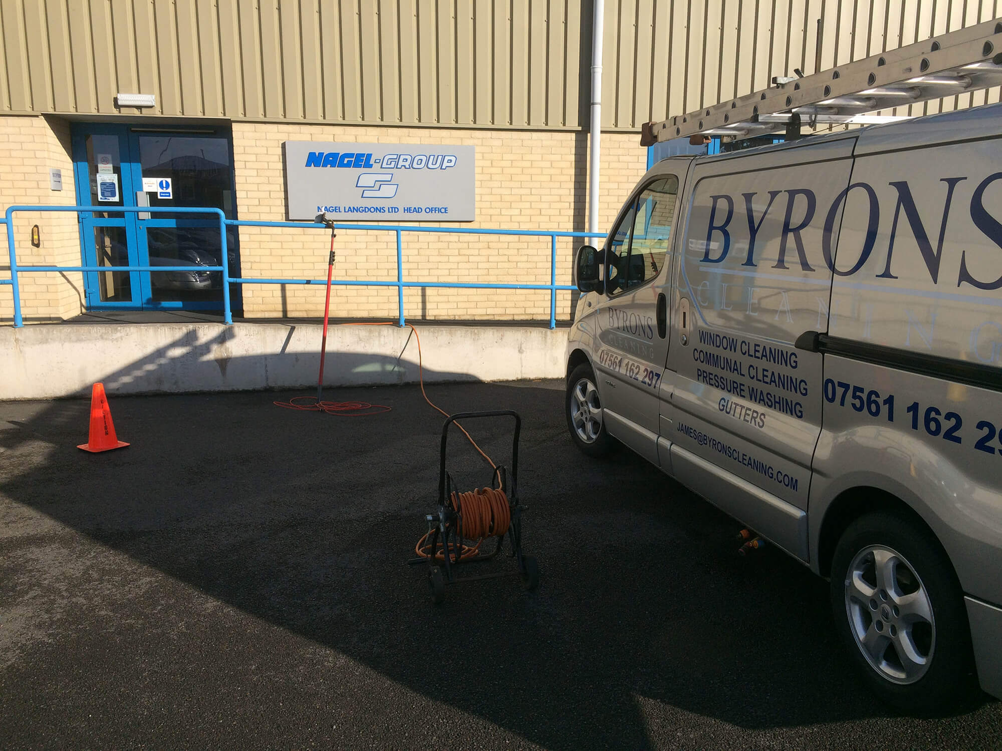 Byrons cleaning van in fron of a commercial window cleaning client's building.