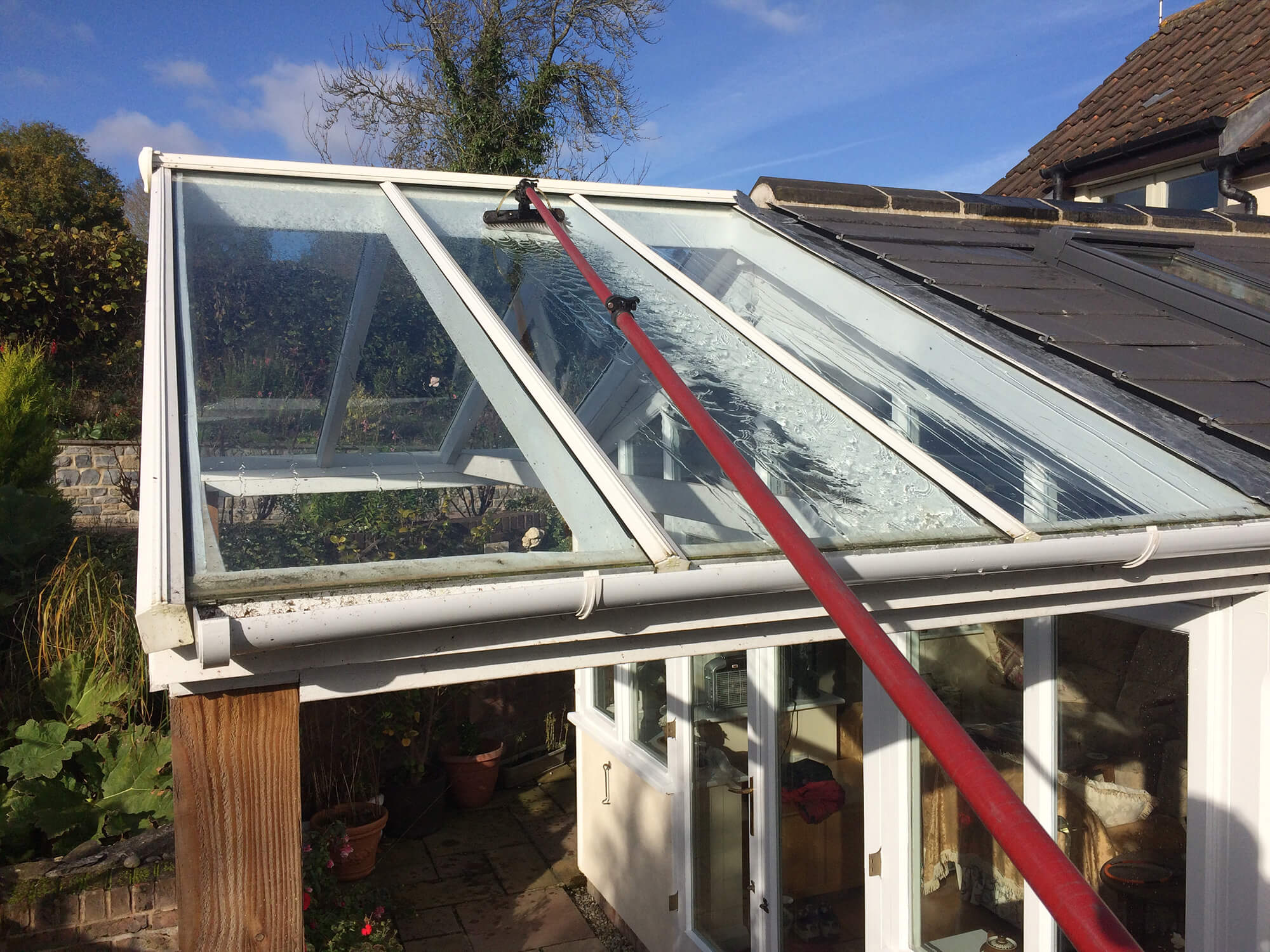 Cleaning a conservatory roof with a reach and wash system